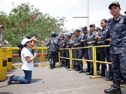 Uma seguidora de Juan Guaidó se ajoelha diante de agentes da Guarda Nacional Bolivariana.