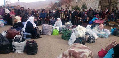 Um grupo de sírios espera a chegada da ajuda humanitária em Madaya.