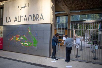 Trabalhadores colocam uma placa informando o fechamento temporário das visitas na entrada da Alhambra, em Granada.