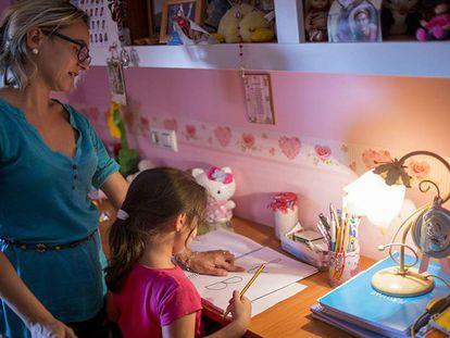 Almudena, de cinco anos, preenche as folhas com as letras do alfabeto ajudada pela mãe.
