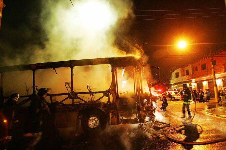 Bombeiros apagam chamas de ônibus incendiado por integrantes do PCC na Vila Madalena, zona oeste de São Paulo, em maio de 2006. Vários ônibus foram incendiados naquela semana.
