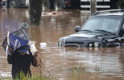 Homem se protege da chuva em via alagada de São Paulo.