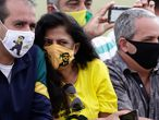 Supporters of Brazil's President Jair Bolsonaro wear face masks amid the new coronavirus pandemic decorated with his image during the president's departure from his official residence, Alvorada palace, Brasilia, Brazil, Monday, May 25, 2020. (AP Photo/Eraldo Peres)
