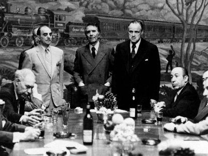 De pé à esquerda, Marlon Brando em uma cena de 'O Poderoso Chefão' (1972), o filme inspirado no romance de Mario Puzo. Em vídeo, o trailer do filme em inglês.