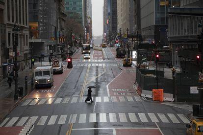 Homem atravessa a 42nd Street em Nova York em 23 de março.