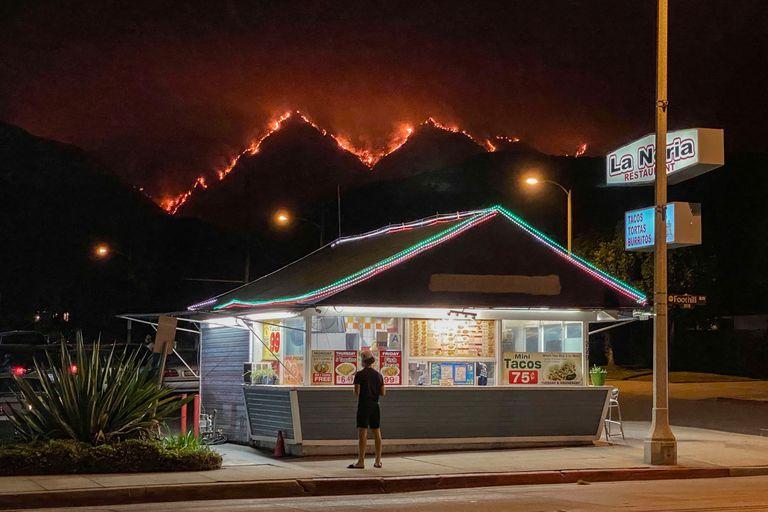 Posto de fast-food na cidade de Monrovia, na Califórnia, com um incêndio florestal ao fundo, na quinta-feira.