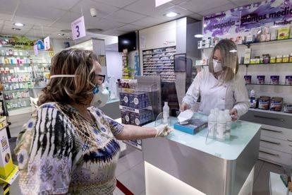 Mulher compra máscara em uma farmácia em Archena (Murcia).