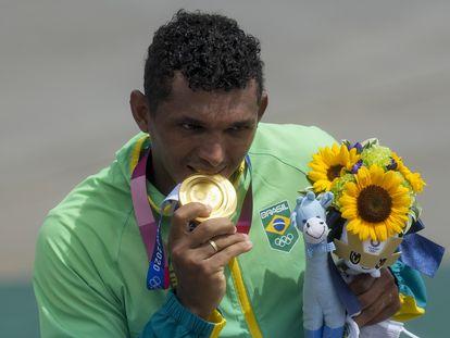 Isaquias Queiroz morde sua medalha de ouro na canoagem.