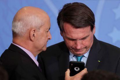 Bolsonaro olha telefone segurado pelo ministro da Secretaria-Geral da Presidência, Luiz Eduardo Ramos, em setembro de 2020.