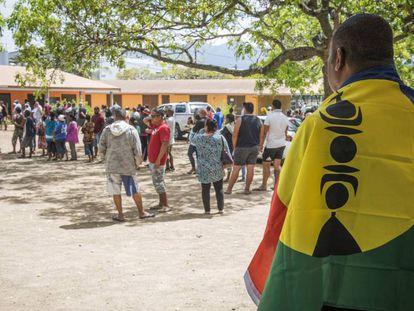 Homem com a bandeira da Nova Caledônia aguarda para votar.