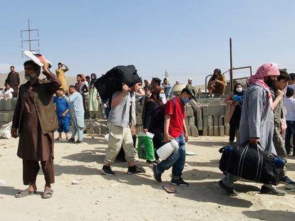 Um grupo de afegãos que tenta fugir do seu país, em frente ao aeroporto de Cabul nesta quinta-feira.