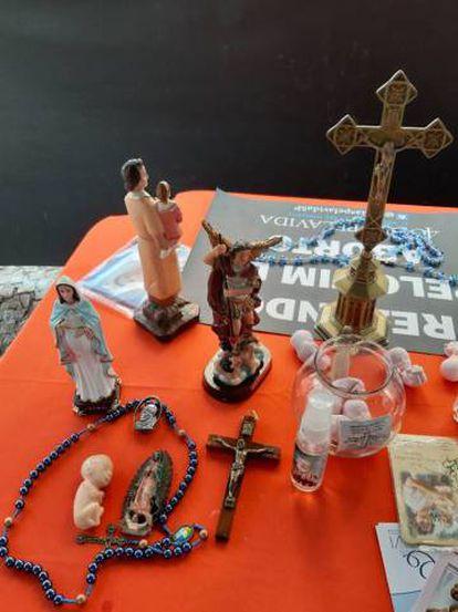 Também há uma mesa com imagens religiosas e crucifixos.