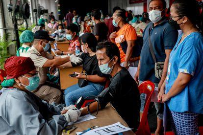 Pacientes passam por checagem médica antes de receber vacina da covid-19 em Medã, Indonésia, nesta sexta.