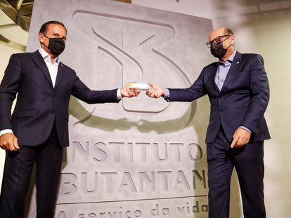 O governador João Doria e o diretor do Instituto Butantan, Dimas Covas, seguram uma dose da coronavac.