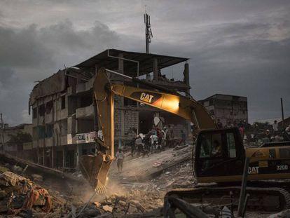 Uma escavadora retira grandes blocos de cimento depois da queda de um edifício em Pedernales