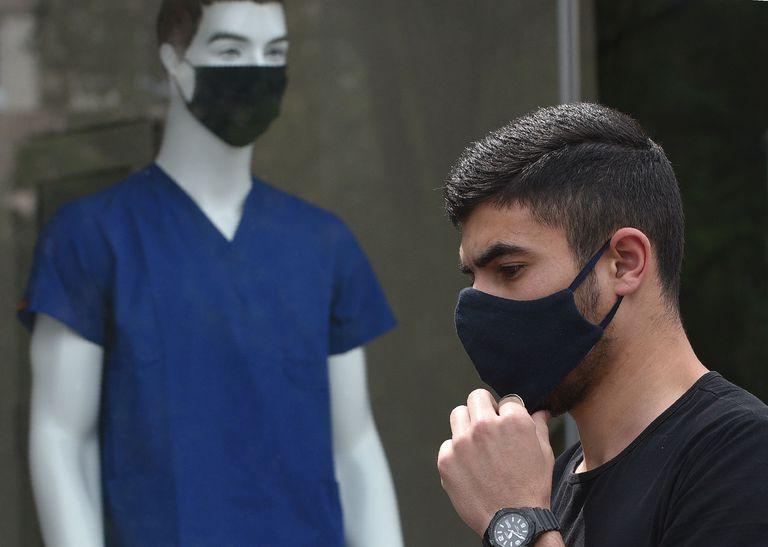 Homem passa por vitrine de uma loja em Erevan, Armênia.