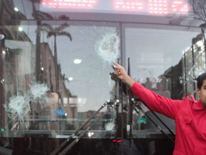 Maduro mostra ônibus danificado pelos protestos.