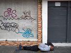 AME5639. QUITO (ECUADOR), 31/07/2020.- Un habitante de calle duerme sin tapabocas mientras militares y policías ecuatorianos patrullan por las calles para contener la aglomeración de personas y detectar las actividades no autorizadas dada la pandemia COVID-19, este viernes en Quito (Ecuador). Las autoridades de Quito continúan sus esfuerzos en el sur de la ciudad para contener la curva de contagios en la capital ecuatoriana, que ya suma 13.342 positivos. EFE/José Jácome