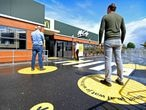 FILE PHOTO: Customers wait outside on social distancing markings at a prototype location of fast food giant McDonald's for restaurants which respect the 1.5m social distancing measure, amid the coronavirus disease (COVID-19) outbreak, in Arnhem, Netherlands, May 1, 2020. REUTERS/Piroschka van de Wouw/File Photo