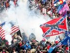 """FILE PHOTO: FILE PHOTO: Tear gas is released into a crowd of protesters, with one wielding a Confederate battle flag that reads """"Come and Take It,"""" during clashes with Capitol police at a rally to contest the certification of the 2020 U.S. presidential election results by the U.S. Congress, at the U.S. Capitol Building in Washington, U.S, January 6, 2021. REUTERS/Shannon Stapleton - RC2N2L9P3COK/File Photo/File Photo"""