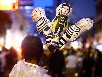 Vendedor exibe bonecos infláveis do juiz Sérgio Moro e de Lula no Rio de Janeiro em Curitiba, no dia 28 de março.