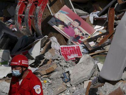 Membro de equipe de resgate trabalha entre escombros de edifício em Tainan.
