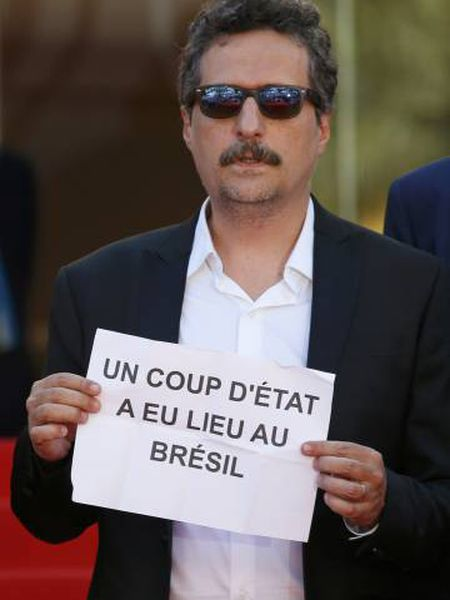 """No tapete vermelho de Cannes, Kleber Mendonça Filho segura cartaz no qual denuncia que """"um golpe de Estado aconteceu no Brasil""""."""