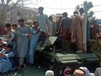 This video frame grab taken from AFPTV footage shows Taliban fighters and local people sitting on top of a captured Afghan National Army (ANA) Humvee vehicle along a street in Jalalabad province on August 15, 2021. (Photo by STR / AFPTV / AFP)
