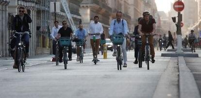 Dezenas de pessoas pedalam pela ciclovia da rue de Rivoli, uma das ruas mais centrais de Paris