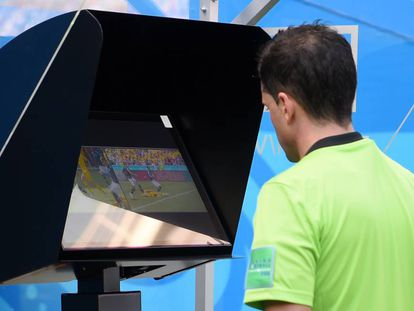O árbitro de França x Austrália revisa uma jogada.