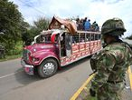 A bus rides near soldiers standing guard at an abandoned barricade blocking the Panamerican highway after a protest against the government triggered by a now abandoned tax reform bill, in Cali, Colombia, on May 10, 2021. - Indigenous and other demonstrators announced Monday the temporary reopening of highways in southwestern Colombia, which had been blocked in the framework of massive protests against the government taking place in the last 13 days, and which have left 27 dead. (Photo by Luis ROBAYO / AFP)