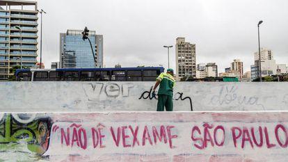 Funcionário apaga pichação contra Doria em São Paulo.