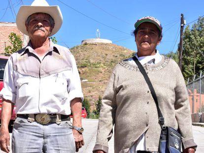 Dois moradores em frente do morro onde será construída a estátua