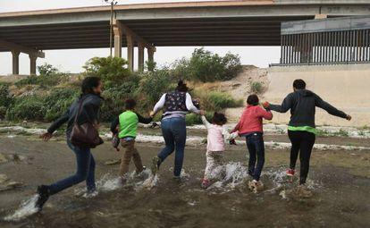 Um grupo de imigrantes cruza o rio entre Cidade Juárez (México) e EL Paso (EUA), nesta segunda-feira