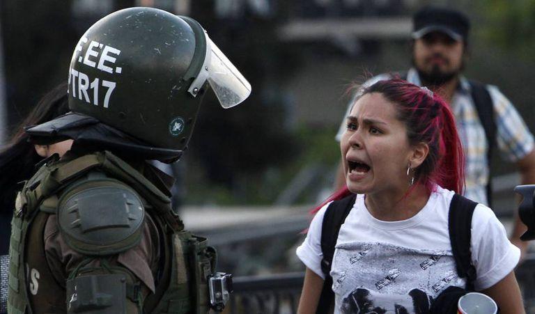 Uma manifestante discute com um carabineiro nos protestos de Santiago.