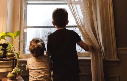 Duas crianças olham por uma janela. Quarentena impõe desafio para pais e filhos.