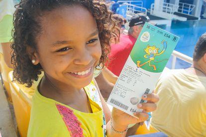 """Fernanda Gomes, de 11 anos, vive com sua mãe e mais dois irmãos no morro da Providência, mas tem """"um monte de irmão"""" que não conhece. Perdeu seu pai assassinado em Niterói, na região metropolitana do Rio, em 2015, o que agravou o trauma que ela diz sofrer toda vez que vê uma arma ou ouve um tiro, o dia a dia do seu bairro. Além da necessidade de ir no banheiro, a pequena relata que sente falta de ar, tremores e febre toda vez que fareja a violência por perto. """"Quando morava em Caxias, tinha tiro na escola e eu vomitava sempre. Hoje não posso ver um policial com arma, passo mal"""". Na van onde relata seus medos viaja um policial da Unidade Pacificadora da Polícia (UPP), Savio Resende, à paisana e desarmado, a quem sua mãe a confiou para visitar pela primeira vez o Parque Olímpico. É a UPP quem, apesar dos problemas que enfrenta com os moradores das comunidades onde atua, está levando as crianças carentes ao estádio."""