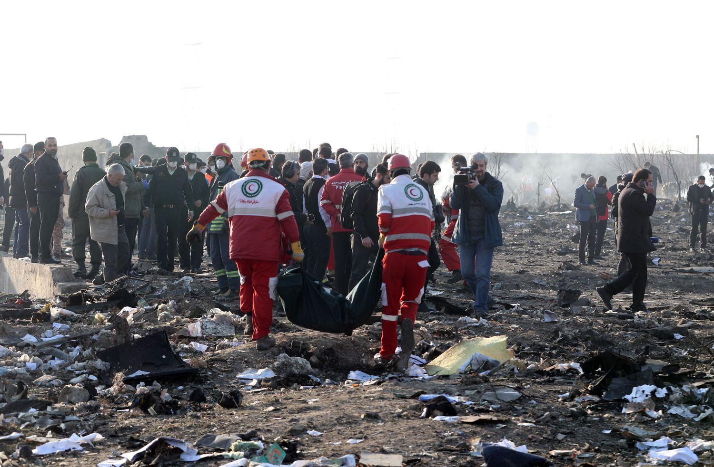 Membros da organização internacional Crescente Vermelho recolhe corpos de vítimas de queda de avião no Irã, em Shahriar.