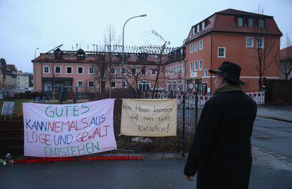 Um homem diante de faixas de protesto contra o incêndio de um hotel, na segunda-feira em Bautzen (Alemanha).