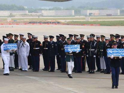 Guarda de honra dos EUA transporta os ataúdes com os restos procedentes da Coreia do Norte.
