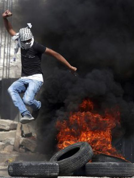 Um homem enfrenta o Exército Israelense em Hebrón.