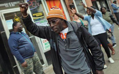 Um homem comemora nas ruas de Baltimore depois da divulgação do relatório da promotora.