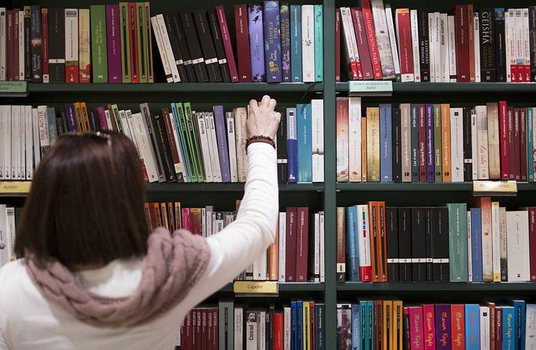 Uma mulher apanha um livro de uma prateleira.