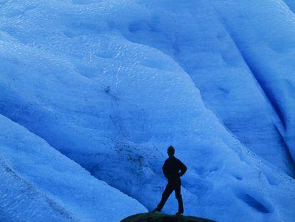 Um turista diante do gelo azul do glaciar Svartisen, ao norte de Noruega.