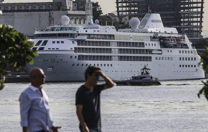 Duas pessoas caminham, tendo o barco Silver Cloud, o cruzeiro dos EUA, ao fundo.