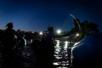 Um agente fronteiriço dos Estados Unidos ajuda uma menina a subir numa lancha no rio Grande, nesta quinta-feira.
