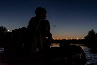 Um haitiano e seu filho atravessam o rio Grande de Ciudad Acuña (México) para Del Rio (EUA), nesta quinta-feira.