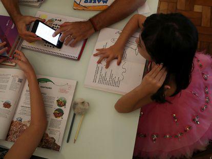 Uma estudante de cinco anos assiste às aulas enviadas pela escola no celular em sua casa, com a ajuda do pai, na cidade paulista de Santo André, em 26 de março, logo após o início da pandemia no Brasil.