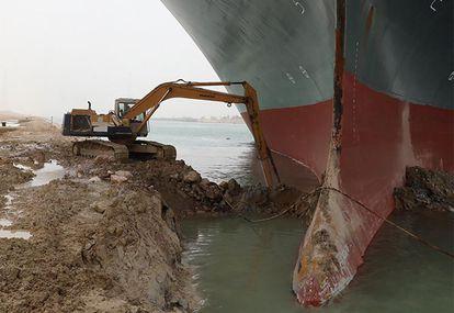 Escavadora retira terra ao redor do navio Ever Given, encalhado no canal de Suez.