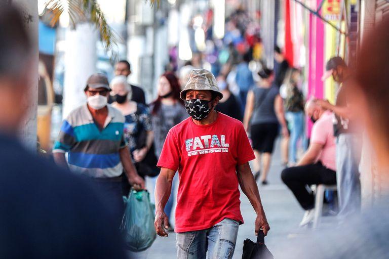 Pessoas com máscaras em frente a lojas fechadas devido à quarentena em São Paulo.